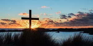 Sunset on lake with cross