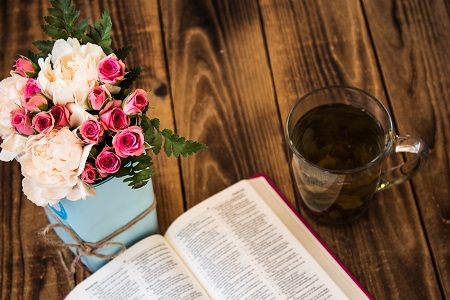 Cup of tea, the bible, and roses