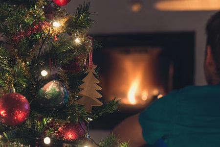 Young man watching a fireplace next to a Christmas Tree