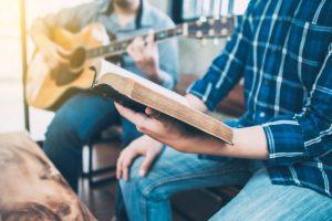 Man reading bible, another playing guitar