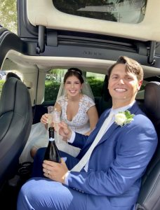 Bride and groom in car with prosecco